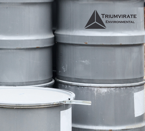 Gray 55 gallon drums with Triumvirate Environmental logo