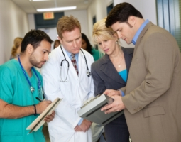 Financial manager reviews data with doctor, nurse and department head
