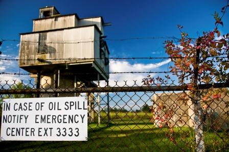 Oil spill warning sign outside fenced in facility