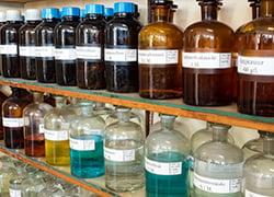Chemical bottles on lab shelf