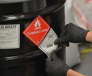 Worker places label on black 55-gallon drum