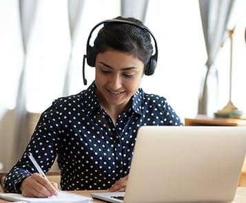 Women wearing headphones at laptop