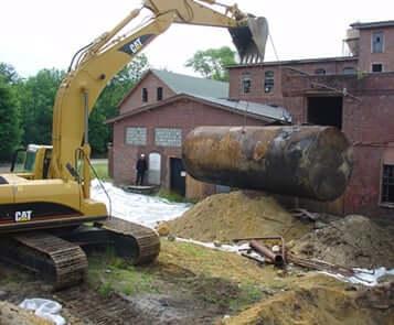 Construction machine raises underground storage tank from ground