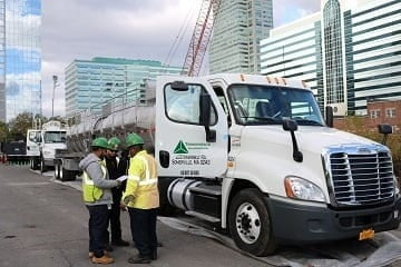 Triumvirate employees stand outside truck at jobsite