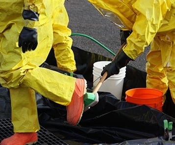 Emergency response workers clean PPE suits