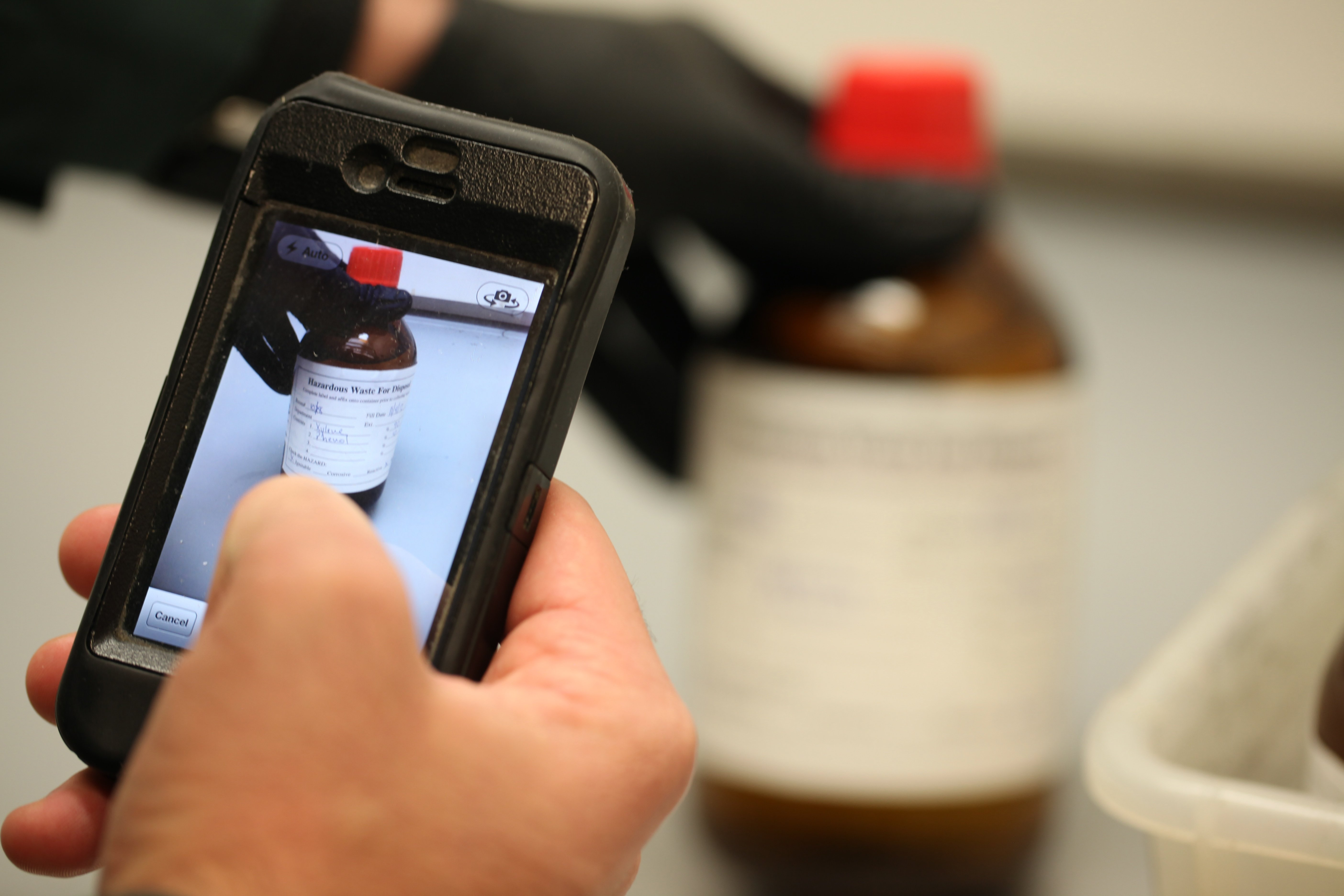 Worker scans chemical bottle label with mobile phone