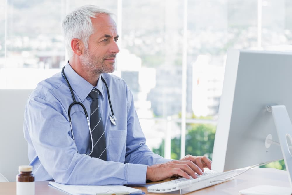 Doctor reviewing hazardous drug info on computer