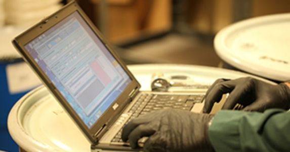 A scientist wearing gloves uses a laptop with chemical inventory software