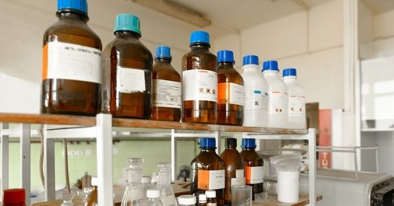 Brown and white chemical bottles lining laboratory shelf
