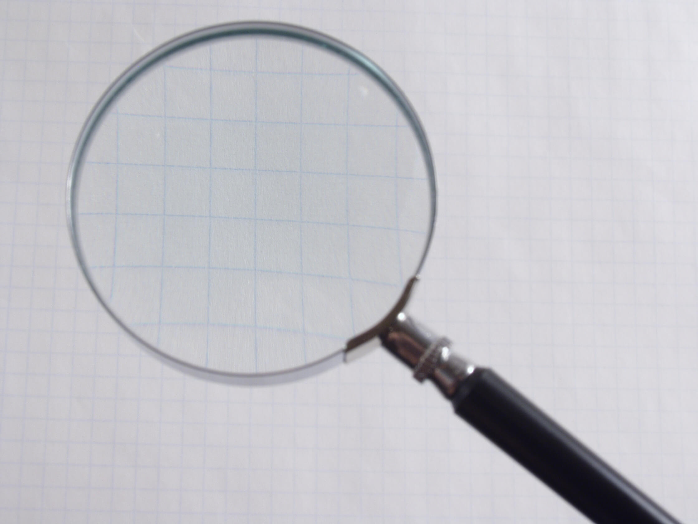 Large magnifying glass over grid paper